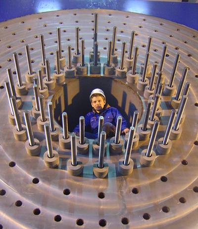 Een testingenieur in het mangat van het opspanblok waar het rotorblad wordt vastgemaakt